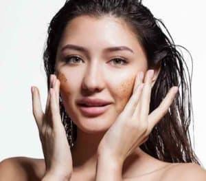 Femme se faisant un gommage ou peeling du visage avec des produits naturels