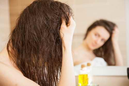 Femme s'appliquant de l'huile de ricin sur ses cheveux abimés et secs