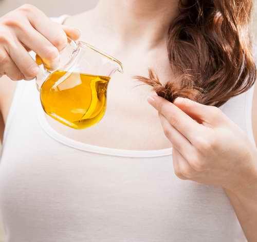 Femme utilisant de l'huile de ricin pour traiter les pointes de cheveux abimés, secs ou fourchues